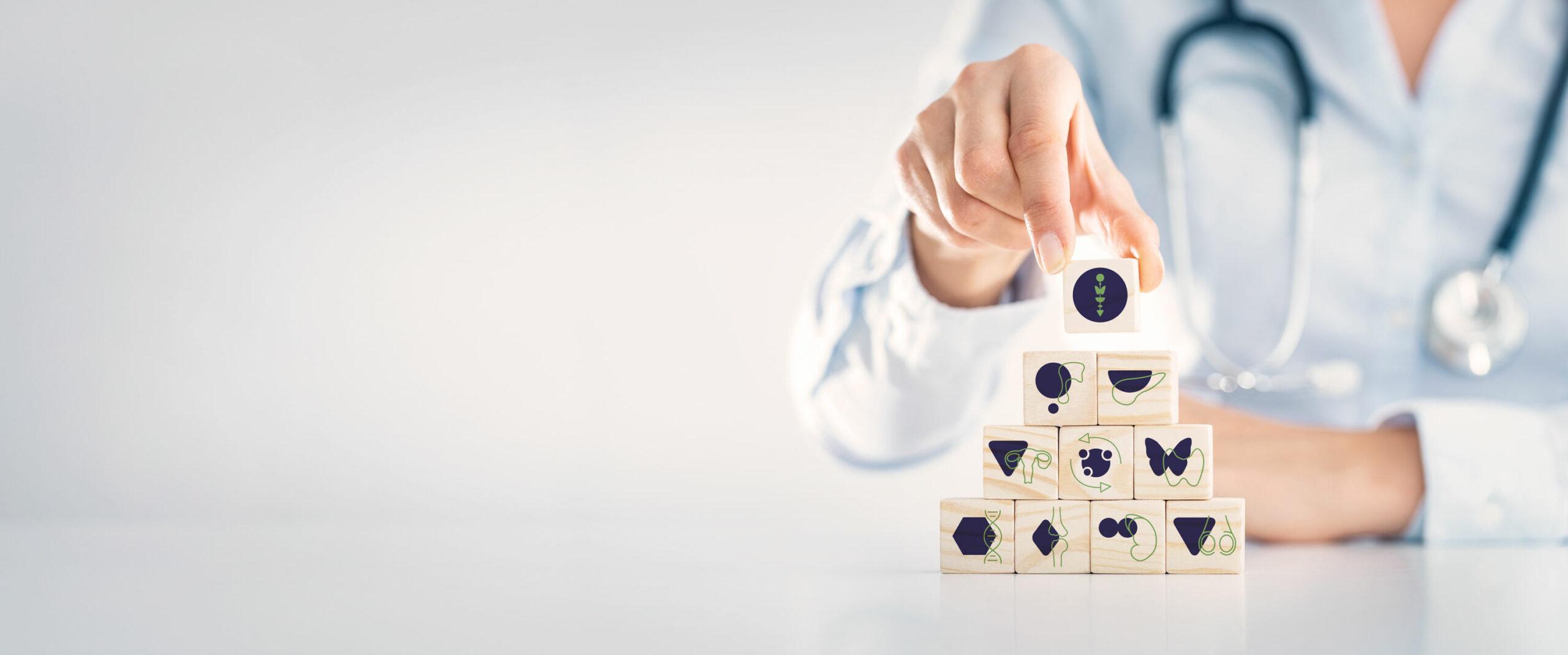 Das Bild zeigt einen Arzt mit Bausteinen. Auf den Bausteinen sieht man das Logo des Endomedicums sowie Icons der Organe: Hirnanhangdrüse, Bauchspeicheldrüse, Gebärmutter, Stoffwechsel, Schilddrüse, Innere Medizin, Knochenstoffwechsel, Nebennieren, Hoden. Endokrinologe Düsseldorf Essen Mönchengladbach Bonn