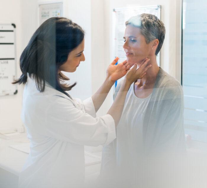 Das Bild zeigt eine Ärztin welche die Schilddrüse einer Patientin abtastet. Endokrinologie Düsseldorf Mönchengladbach Essen Bonn