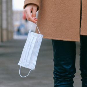 Das Bild zeigt eine Frau mit Maske in der Hand. Es steht für die Corona Verhaltensregeln des Endomedicums Düsseldorf. Endokrinologie und MVZ für Hormon- und Stoffwechselerkrankungen.