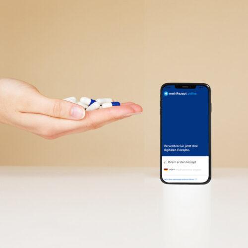 Das Bild zeigt eine weibliche Hand mit Kapsel in der Hand samt Smartphone auf welchem die App: Mein Rezept Online geöffnet ist. Das Bild steht für unser digitales Angebot in Düsseldorf des Endomedicums - MVZ für Innere Medizin und Hormon- und Stoffwechselerkrankungen